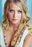 Sehr schöne blonde Frau mit dem langen gelockten Haar und den blauen Augen Stockfoto