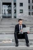 Sehr schöne dreidimensionale Abbildung Der junge Mann, der auf der Straße sitzt und hält Ihr compu Lizenzfreie Stockbilder