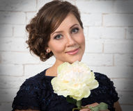 Sehr schöne dunkelhaarige junge Frau mit weißer Blume Stockfotos