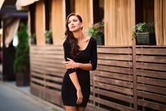 Sehr schöne junge Brunettefrau, die in der Straße trägt Lizenzfreies Stockfoto