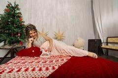 Sehr schöne und sexy Frau in einem rosa Kleid im Dekor des neuen Jahres, geschaukelt in der Art des neuen Jahres lizenzfreie stockfotos