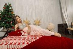 Sehr schöne und sexy Frau in einem rosa Kleid im Dekor des neuen Jahres, geschaukelt in der Art des neuen Jahres lizenzfreie stockfotografie