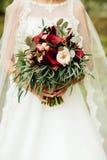 Sehr schöner Hochzeitsblumenstrauß in den Händen der Braut Stockfotografie