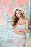 Sehr schönes blondes Mädchen in einem Spitzekleid mit einem Kranz des Flusses Stockfotografie