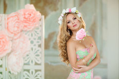Sehr schönes blondes Mädchen in einem Spitzekleid mit einem Kranz des Flusses Stockfoto