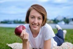 Sehr schönes kaukasisches Modell, das roten Apfel im Park isst Draußen Porträt des recht jungen Mädchens Stockfotografie