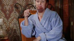 Sehr schönes Mädchen in einem Bademantel trinkt Tee stock video footage