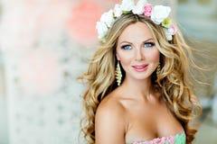 Sehr schönes und sinnliches blondes Mädchen, lächelnd, mit einem Kranz O Stockfotos