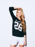 Sehr schönes Mädchen mit dem langen blonden Haar, das auf einem weißen Hintergrund aufwirft Sie hob ihre Hand über ihrem Kopf und Stockfotos