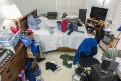 Sehr unordentliches Jungen-Schlafzimmer stockfotos