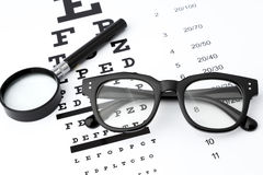 Sehvermögentest mit schwarzem kleinem Vergrößerungsglas, schwarze Gläser und snellen Diagramm Stockfotografie