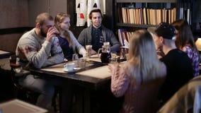 Sei amici dello studente dei pantaloni a vita bassa che comunicano in caffè archivi video