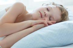 Sei anni del bambino che dorme a letto Immagini Stock