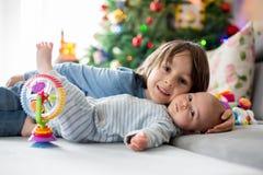 Sei anni del ragazzo prescolare, giocante a casa con le sue sedere neonate Immagine Stock Libera da Diritti