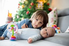 Sei anni del ragazzo prescolare, giocante a casa con le sue sedere neonate Fotografia Stock Libera da Diritti