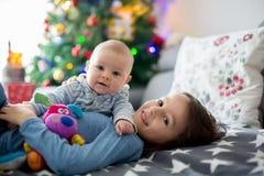 Sei anni del ragazzo prescolare, giocante a casa con le sue sedere neonate Immagini Stock