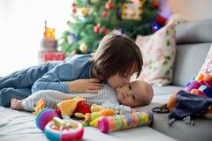 Sei anni del ragazzo prescolare, giocante a casa con le sue sedere neonate Immagine Stock