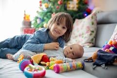 Sei anni del ragazzo prescolare, giocante a casa con le sue sedere neonate Fotografia Stock