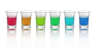 Sei bevande differenti di colore in vetri su fondo bianco Fotografia Stock Libera da Diritti