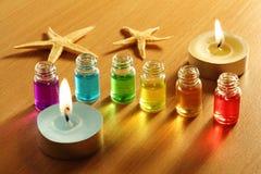 Sei bottiglie con gli oli, le candele e le stelle marine dell'aroma Fotografia Stock Libera da Diritti