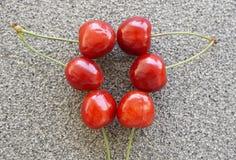 Sei ciliege rosse fresche su un fondo grigiastro Immagini Stock