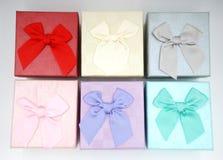 Sei contenitori di regalo con la cravatta a farfalla sulla cima fotografia stock