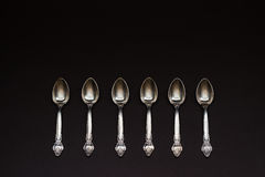 Sei cucchiai d'argento in una fila su fondo nero Immagini Stock