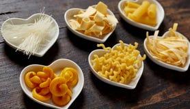 Sei cuori hanno modellato le ciotole di pasta cruda sulla tavola Immagine Stock
