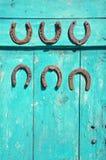 Sei ferri di cavallo arrugginiti antichi sulla porta di granaio di legno verde dell'azienda agricola Fotografie Stock Libere da Diritti