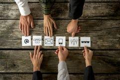 Sei genti che dispongono le carte bianche con le varie icone del contatto in una r Fotografia Stock