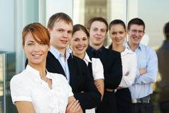 Sei giovani businesspersons stanno levando in piedi in una riga Fotografie Stock Libere da Diritti