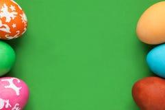 Sei ha colorato le uova di Pasqua sui lati del telaio contro fondo verde Fotografia Stock
