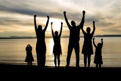 Sei membri della famiglia al tramonto della siluetta della spiaggia immagini stock libere da diritti