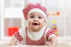 Sei mesi della neonata che si trova sul tappeto sul pavimento in scuola materna Fotografia Stock Libera da Diritti