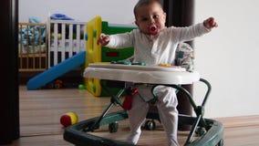 Sei mesi svegli arround di camminata e di salto del neonato nel camminatore anziano del bambino, facente le espressioni divertent video d archivio