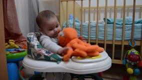 Sei mesi svegli del neonato nel camminatore che tiene il giocattolo arancio del polipo e che impara camminare video d archivio