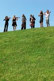 Sei musicisti giocano i violini contro il cielo Immagini Stock Libere da Diritti