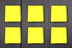 Sei note gialle dell'appunto su fondo di legno nero Immagini Stock