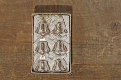 Sei piccole campane di natale in scatola sulla tavola Fotografie Stock
