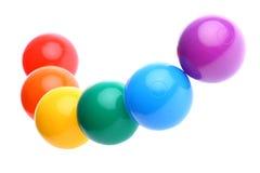 Sei sfere di plastica colorate lucide del giocattolo isolate immagini stock
