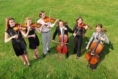 Sei violinisti si levano in piedi il semicerchio su erba e su gioco Fotografia Stock Libera da Diritti