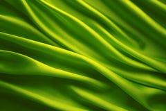 Seidengewebe-Hintergrund, grüner wellenartig bewegender Stoff Lizenzfreie Stockbilder