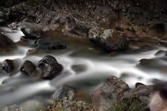 Seidiges glattes Wasser über Felsen Stockfoto