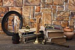 Seien Sie auf dem Tisch: alte Bücher, eine Wachskerze in einem Bronzekerzenständer, ein keramischer Topf, eine Taschenuhr, Quaste Lizenzfreies Stockbild