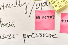 Seien Sie der Active, der auf die rosa Papieraufkleber geschrieben wird, die zu einer Flip-Chart befestigt werden stockbild