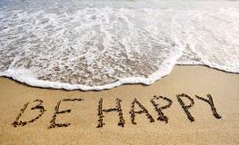 Seien Sie die glücklichen Wörter, die auf Sand-positives denkendes Konzept des Strandes geschrieben werden Lizenzfreie Stockfotos