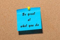 Seien Sie groß an, was Sie tun - die Motivkonzeptmitteilung festgesteckt an der KorkenAnschlagtafel Lizenzfreie Stockfotografie