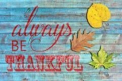 Seien Sie immer auf blauem hölzernem Hintergrund dankbar