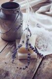 Seife, Lavendel, Salz und alte Dose auf hölzernem Brett Stockfotografie