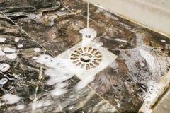 Seifen Sie den Schaum und Wasser ein, die in Badezimmerentwässerungsloch fließen Lizenzfreie Stockfotos